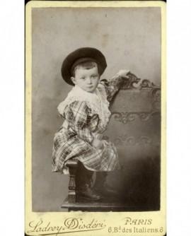 Enfant en robe écossaise et chapeau rond