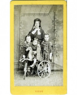 Femme posant derrière trois enfants, l'un étant sur un tricycle à cheval (jouet)