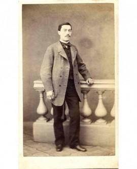 Homme moustachu debout, appuyé à une balustrade