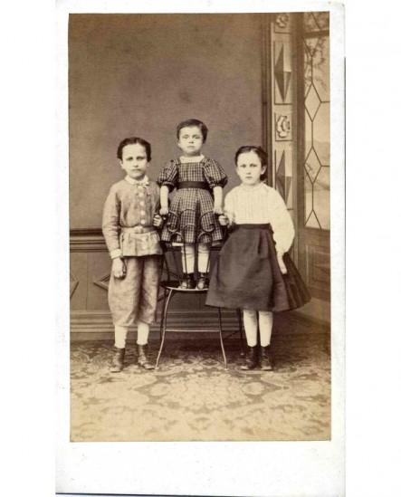 Fratrie de trois enfants: le plus jeune sur une chaise entre les deux aînés