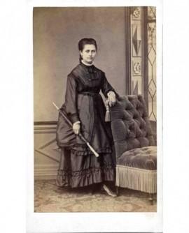 Jeune femme en robe avec ombrelle, accoudée à un fauteuil