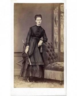 Jeune femme en robe avec ombrelle accoudée à un fauteuil