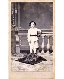 Jeune garçon en costume à culotte courte et ceinturon, accoudé à une balustrade