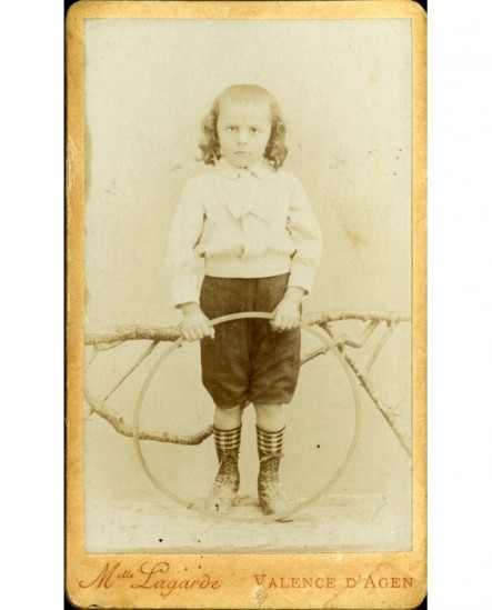 Petit garçon à cheveux longs avec cerceau (jouet)