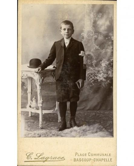 Communiant (en culotte courte), missel à la main, chapeau melon posé près de lui