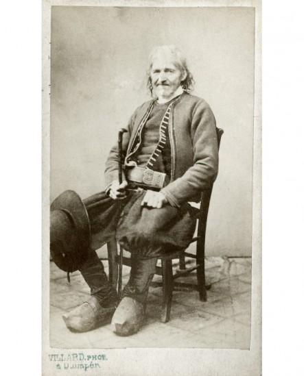 Paysan breton assis canne à la main chapeau rond sur le genou
