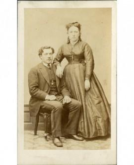 Couple: homme assis, femme debout appuyée sur son épaule