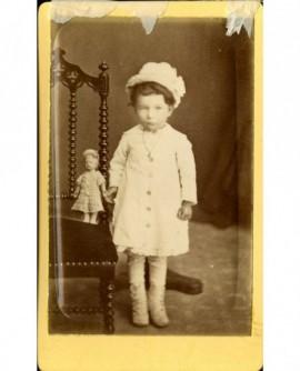 Fillette en chapeau, tenant sa poupée debout sur une chaise