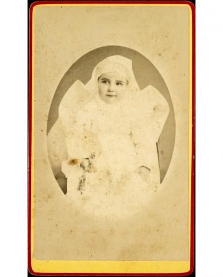Jeune enfant habillé de blanc, un hochet dans la main droite