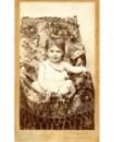 Bébé en chemise, épaule dénudée, assis dans un fauteuil