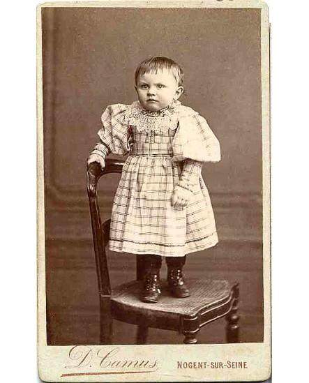 Enfant en robe debout sur une chaise