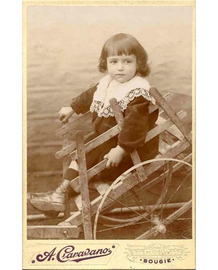 Enfant en robe à col de dentelle dans une charrette