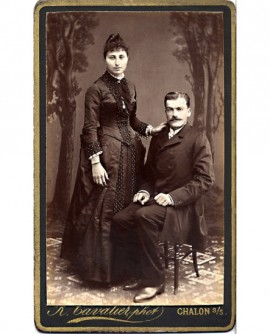 Couple: homme moustachu assis, femme debout appuyée sur son épaule