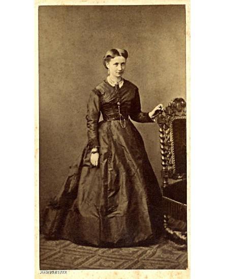 Jeune debout, la main gauche appuyée sur une chaise