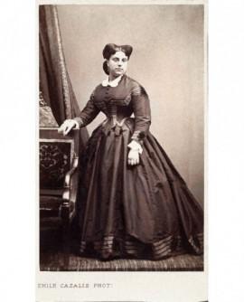Jeune femme en robe accoudée à un fauteuil