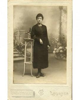 Femme en robe debout, accoudée à une console, au milieu de fleurs