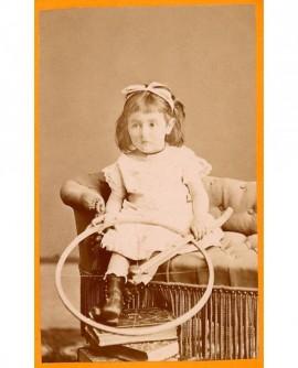 Fillette assise sur un fauteuil tenant baguette et cerceau (jouet)