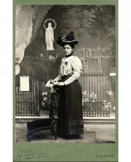 Femme en chapeau devant la grotte de Lourdes