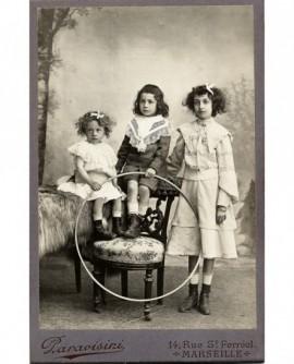 Groupe de trois enfants tenant un grand cerceau (jouet)