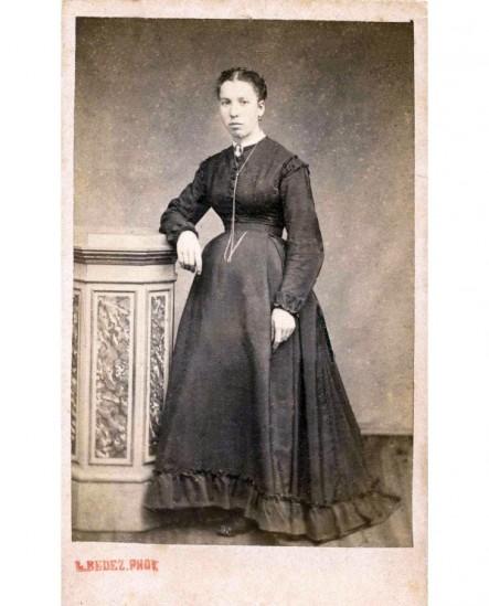 Femme en robe posant accoudée sur un piédestal