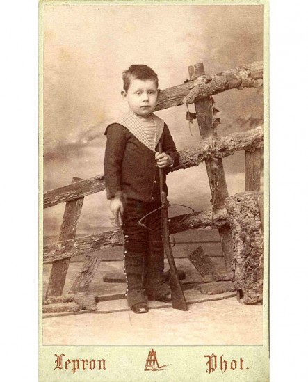 Enfant en col marin debout avec un fusil (de bois)