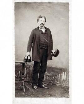 Homme moustachu présentant une paire de chaussures (cordonnier)