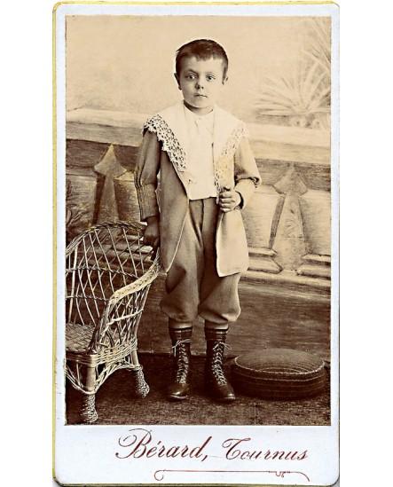 Jeune garçon en bottines appuyé sur un petit fauteuil en rottin