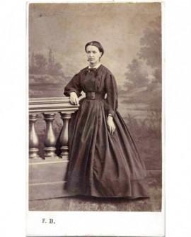 Femme en robe accoudée à une balustrade