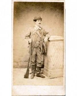 Chasseur en bottres et chapeau melon posant avec son fusil