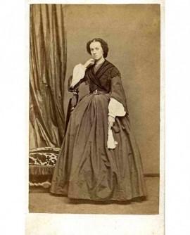Femme accoudée à un fauteuil, un mouchoir à la main
