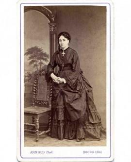 Femme debout, appuyée sur une chaise, une grande croix au cou