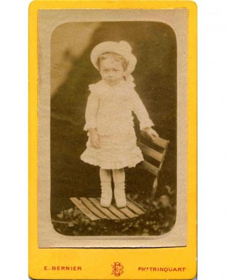 Fillette en robe blanche et chapeau debout sur une chaise de jardin