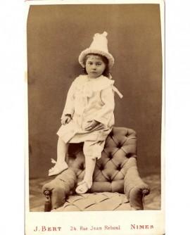 Fillette déguisée en pierrot assise sur un fauteuil