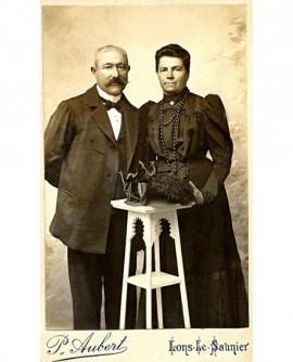 couple : mari moustachu et femme en robe noire debout, manchon