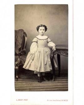 Fillette debout en robe, appuyée sur une table