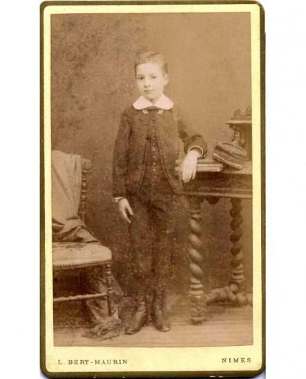 Jeune garçon accoudé à une table, des livres sous le coude
