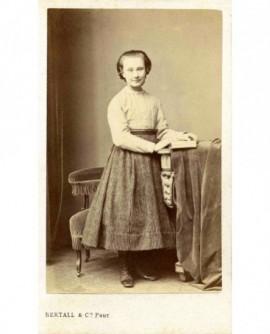 Jeune fille debout tenant un livre ouvert
