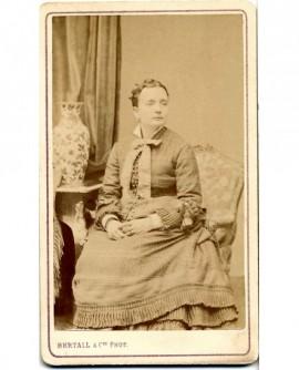 Femme assise sur une fauteuil, un vase de chine près d'elle