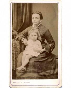 Femme assise, un bébé en chemise sur les genoux