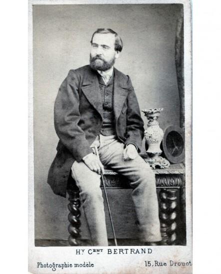 Homme barbu assis avec canne