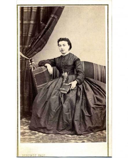 Femme en robe assise sur un canapé, un livre à fermoir à la main