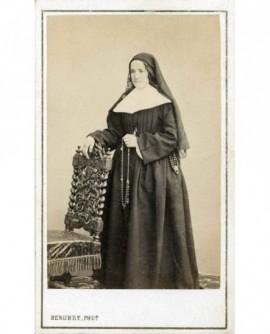 Religieuse debout tenant son chapelet, appuyée sur une chaise