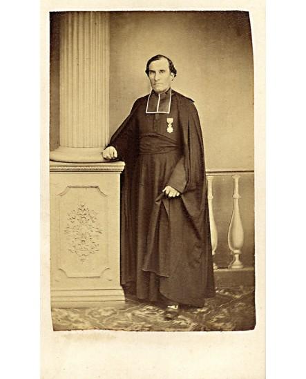 Ecclésiastique décoré de la Légion d'honneur debout, appuyé à une colonne