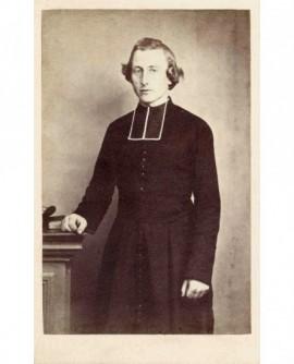 Ecclésiastique à cheveux bouclés debout, brévaire près de lui