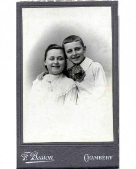 Frère et soeur souriant, enlacés