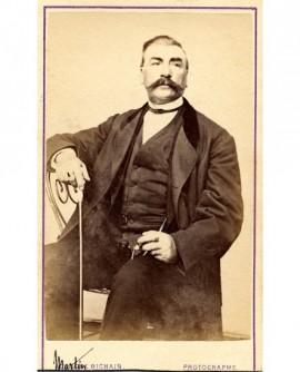 Portrait d'un homme à moustache assis, canne d'une main, cigare de l'autre