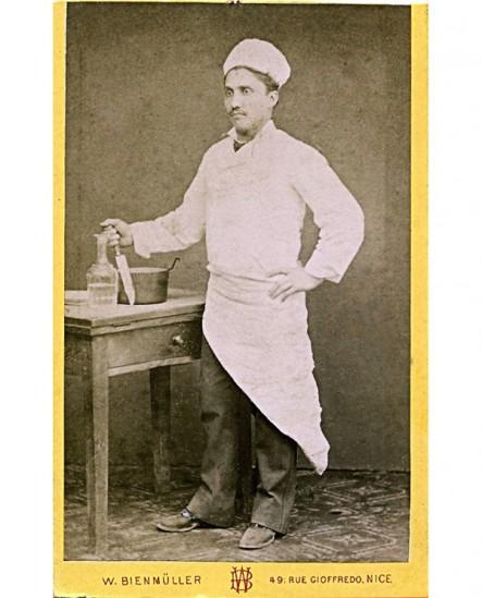 Cuisinier posant un couteau planté dans la table à découper