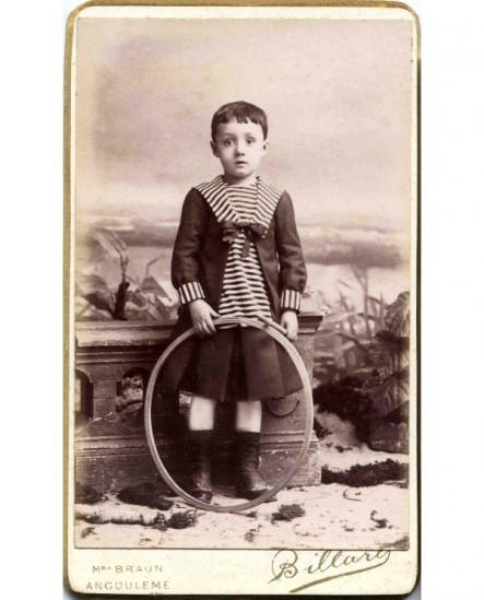 Garçon debout en robe de marin tenant baguette et cerceau (jouet)