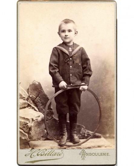 Garçon en costume marin avec baguette et cerceau (jouet)