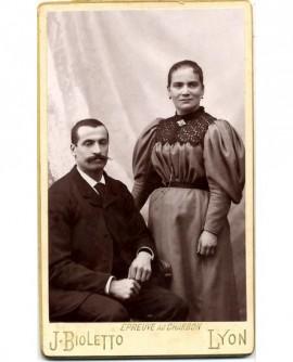Couple: homme moustachu assis, femme debout